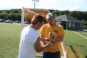 Orange Talent captain Gino accepts the Kickin' Cancer championship trophy